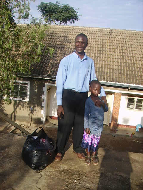 Eagles Wings Children's Village's social worker, Allan Kisakye, is seen here with EWCV's first child, Fatuma.