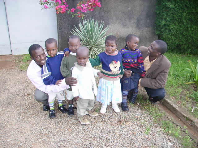 Five EWCV Children with Staff Members, Moses and Allan