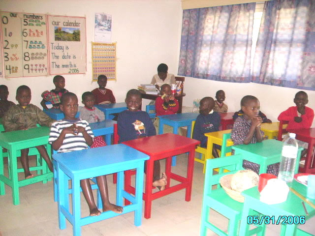 Thirteen EWCV Children Seated at Colourful Desks