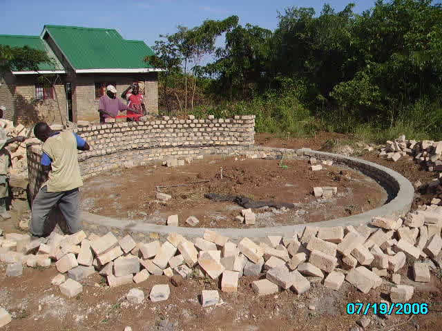 Three Workers Building Dining Hut Walls out of Bricks
