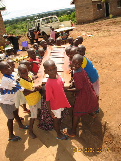 Seventeen Children Entusiastically Helping to Carry Door to the Dining Hut