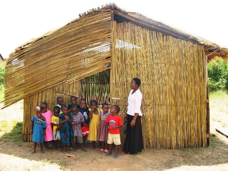 Nursery Teacher and Students in front of One-Room Building