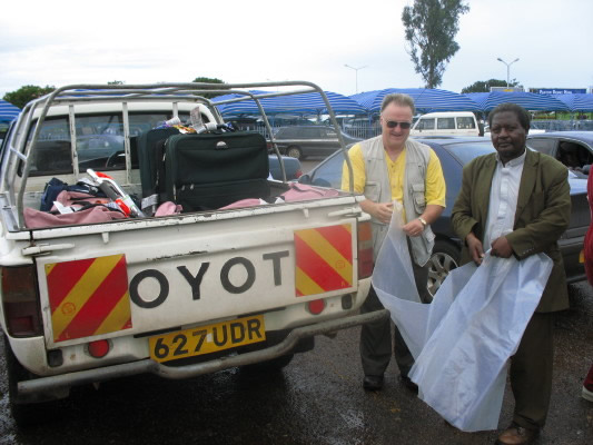 Bill and Rev. Muwonge Packing Luggage into EWCV Truck