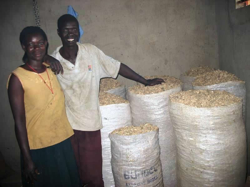 Two EWCV Staff Members beside the harvest of g. nuts and beans.