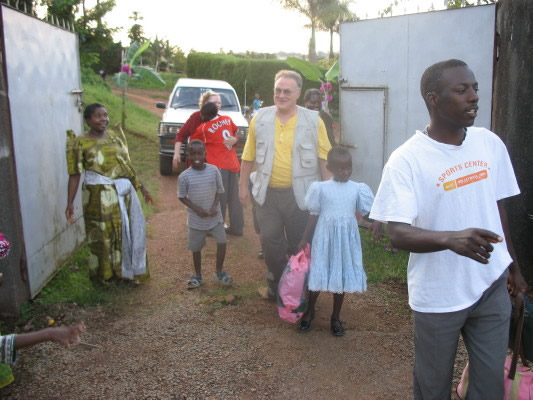 Bill and Ann Being Greeted by Staff and Family #2 Children at their Home in Soweto, Masaka