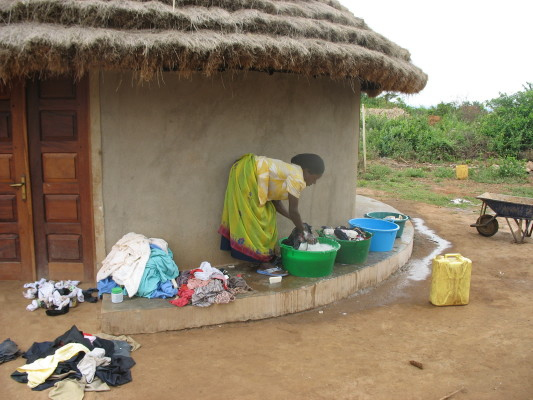 Sylvia, staff member, washing Family #1's Clothes
