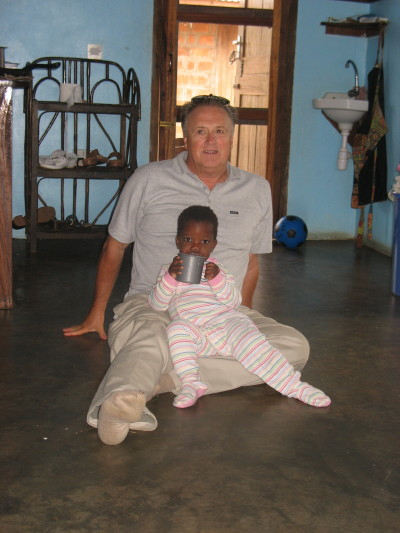 Bill Sitting on Floor with a Child in Kasan New Hope Orphanage