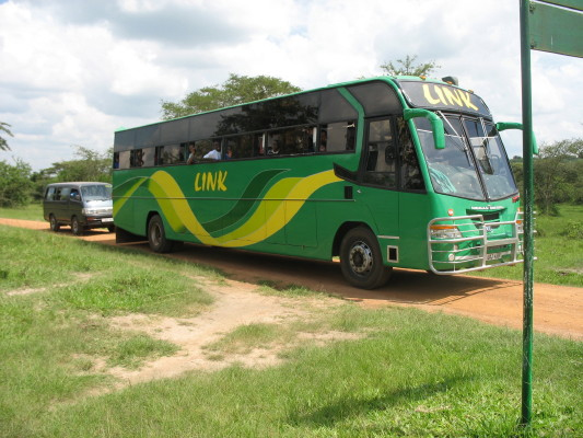 Green Bus Arriving at Park Entrance