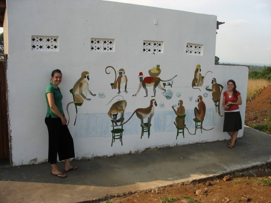 Two Volunteers Standing by Mural of Nine Delightful Monkeys, Painted by Mary on the Latrine's White Exterior