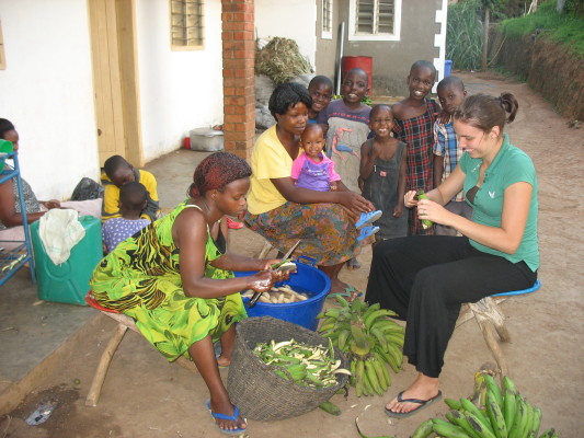 Volunteer, Ashley, Helping Staff Peel Matooke, with Five Children Watching