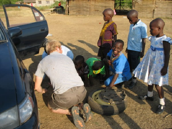 Volunteer Steve and Tatta Aaron Changing a Tire as Five Children Watch