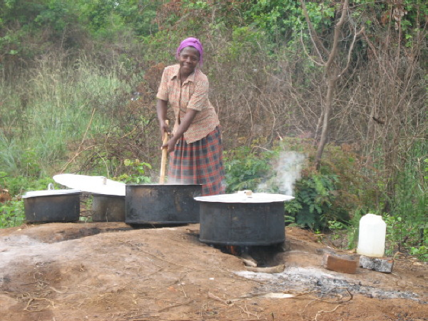 Cook Preparing Food in Large Metal Pots Placed over Fire Pits