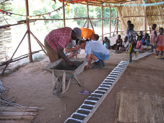 Three Adults Helping EWCV Children Make Handprints in Cement