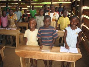 Smiling Children Standing at their Desks