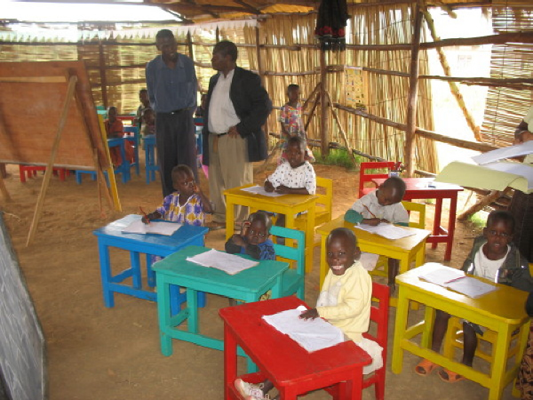 EWCV Youngest Students Seated at Individual Desks of Red, Blue, Green, and Yellow
