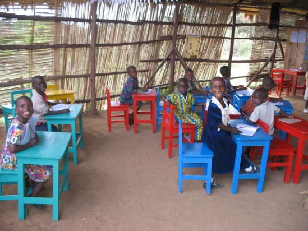 Smiling Nursery Students at Desks