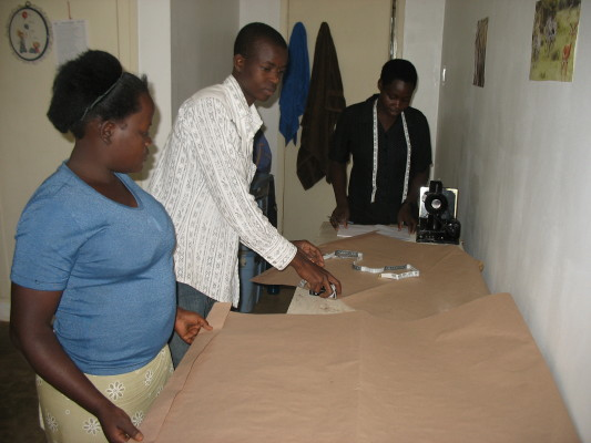 Two young women, sponsored by EWCV, are learning from a tailor how to make the 160 school uniforms that EWCV needs.