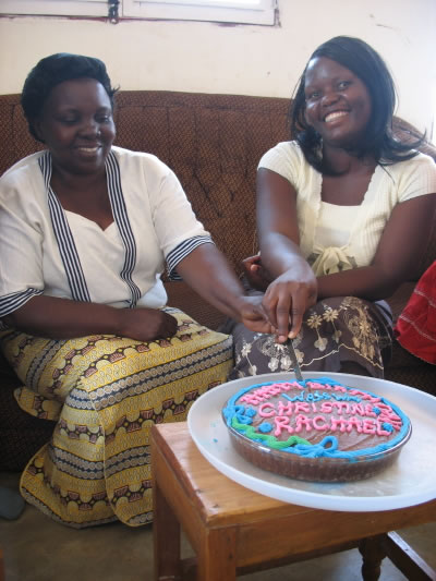 Two Smiling, Female Staff Members Cutting their Birthday Cake