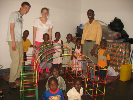 Nine EWCV children, two American university students, and Uncle Allan makge a structure from donated play straws. from the USA