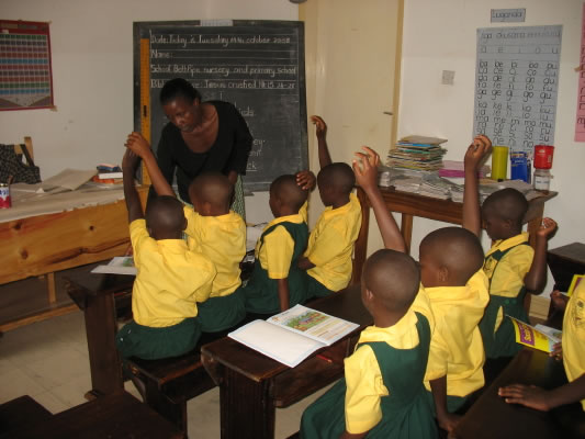 Teacher and Primary One Students, Seated in Desks, Hands Raised