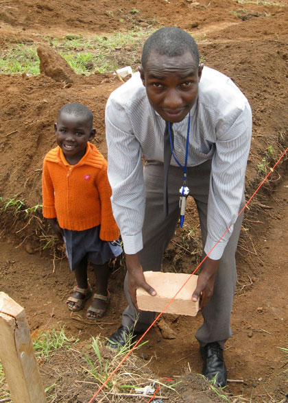 Highschool Accountant Sam, with Elisha, Lays Another Corner Brick of EWCV High School