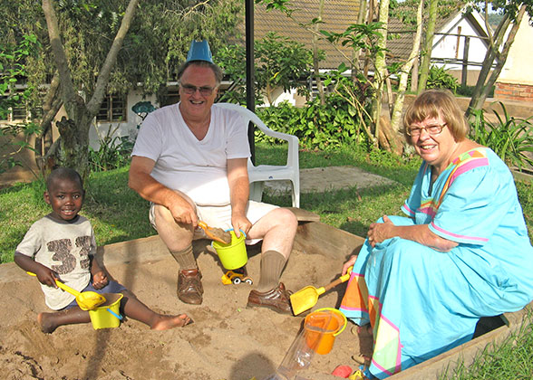 Bill and Ann play with Elisha in a sandbox at their rented home in Masaka.