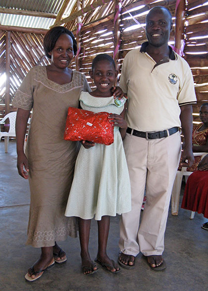 Girl holding Birthday Gift, with House Parents on Either Sides