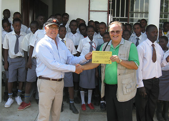 Director of Classrooms for Africa presents Bill with plaque for the EWCV high school.