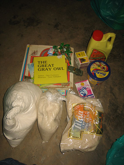 Contents of Gift Bag - items such as maize flour, cooking oil, pencil, sugar, pencil, book, toy, candy