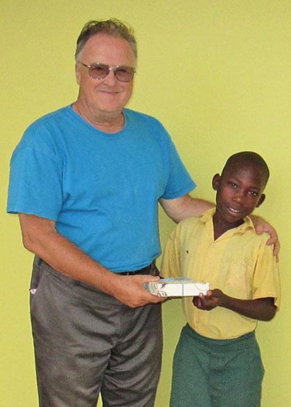 Ja Ja Bill gives a birthday present to an EWCV child.