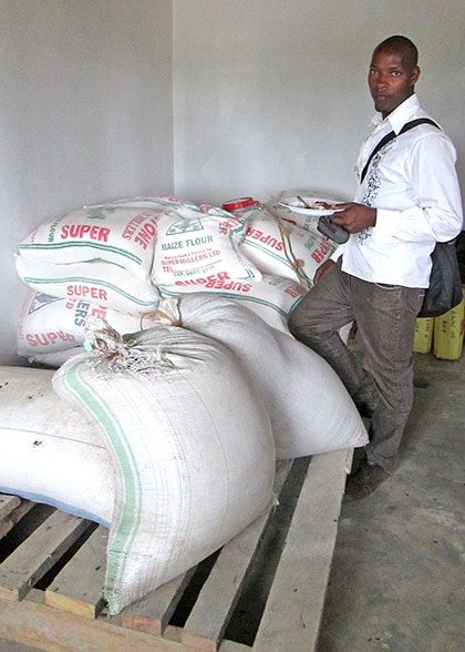 EWCV Maintenance Officer beside Bags of Maize Flour in Storage Room