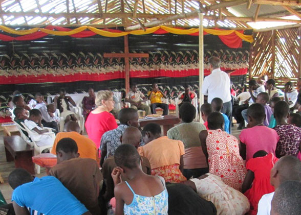 Dr. Macris Praying for Children at their Birthday Celebration