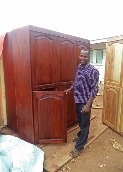 Carpenter Paul beside One of Twelve Cabinets Built for the Sleeping Huts