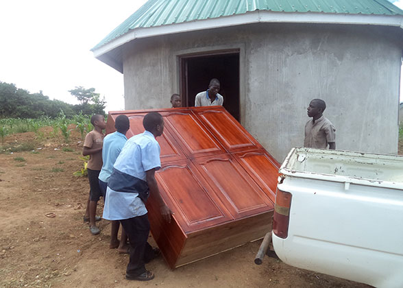 Children and Adults Moving a Cabinet into a Sleeping Hut