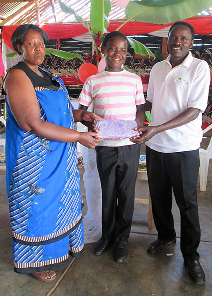 Boy Holding Birthday Gift of New Clothes , with his House Parents