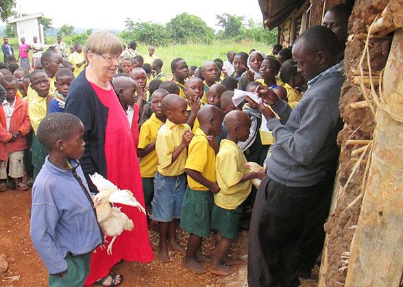 Ja Ja Ann with Children Receiving Chickens