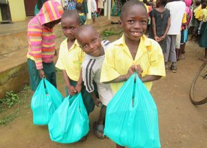 Children with Christmas Gift Bags that contain useful items and sweets!