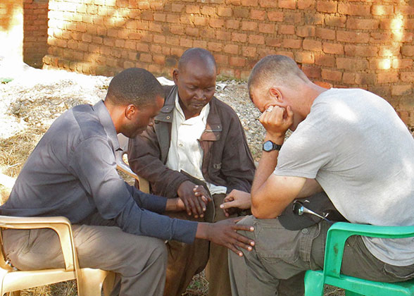 Two village men pray with Jonathan.