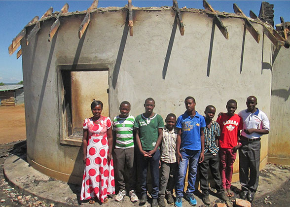 House Parents and Six Boys in front of the sleeping hut that needs a new roof because of a recent fire.