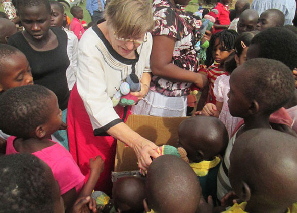 Ja Ja Ann Peckham Handing Out Knitted Dolls to Happy Children