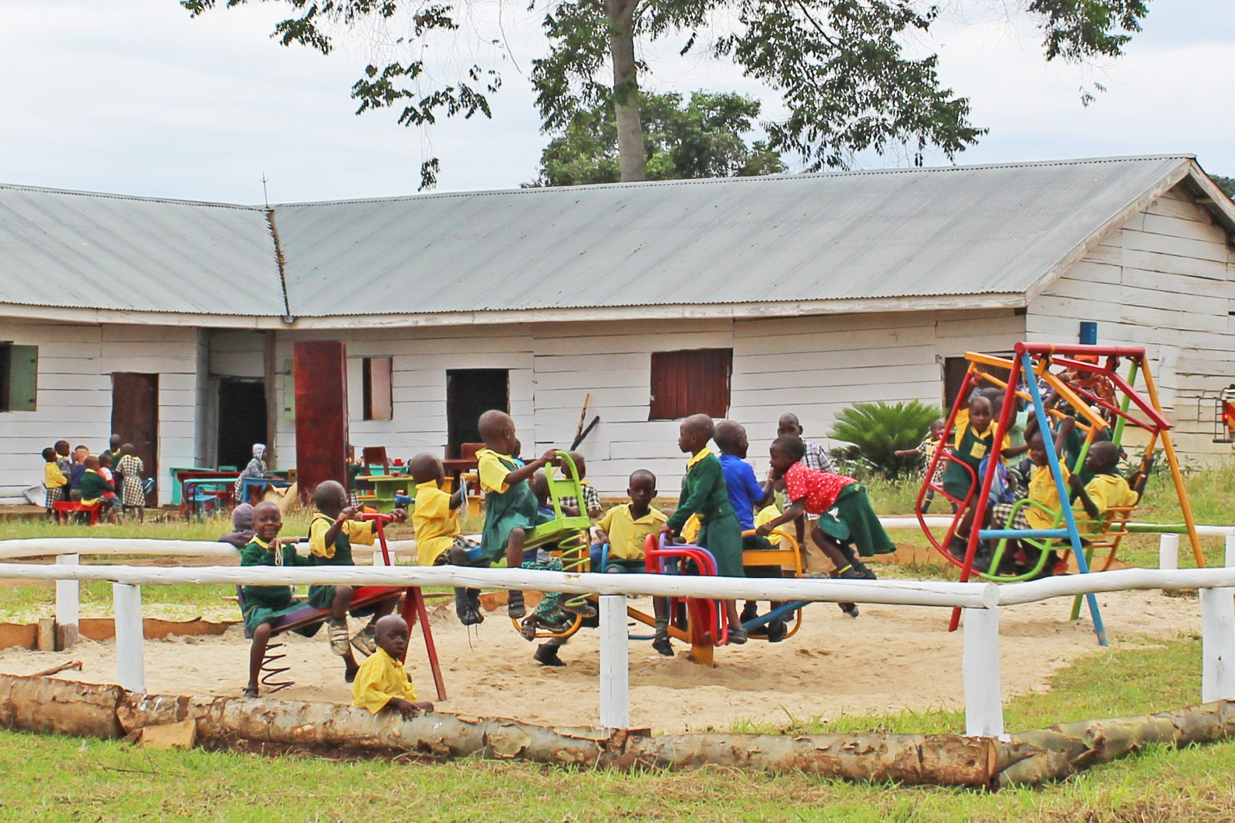 Nursery Class Children Playing on Newly Installed Playgound Equipment - a Seesaw, a Merry-Go-Round, and a Bench Swing