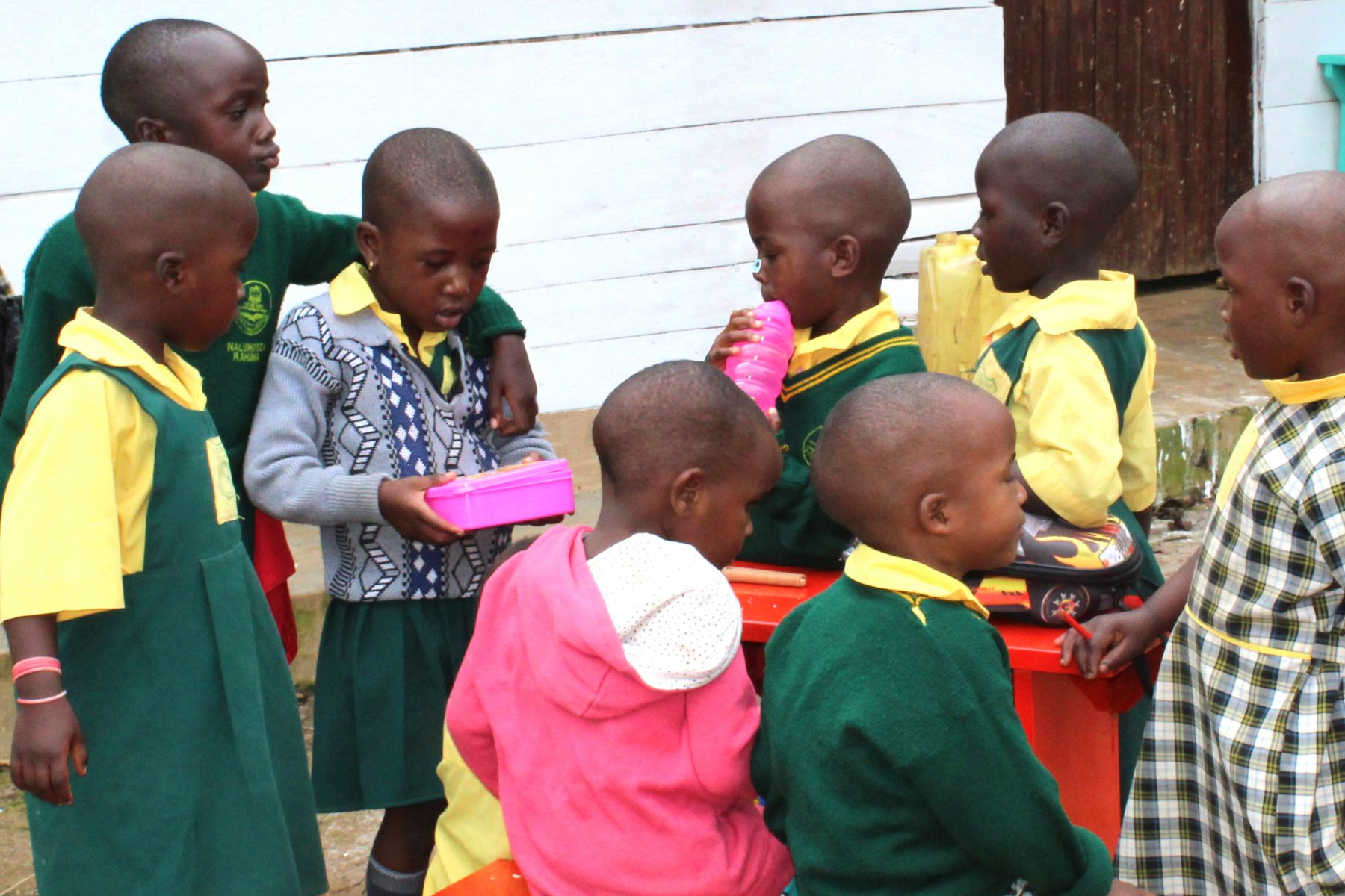 Seven Nursery Students Looing at their New School Supplies