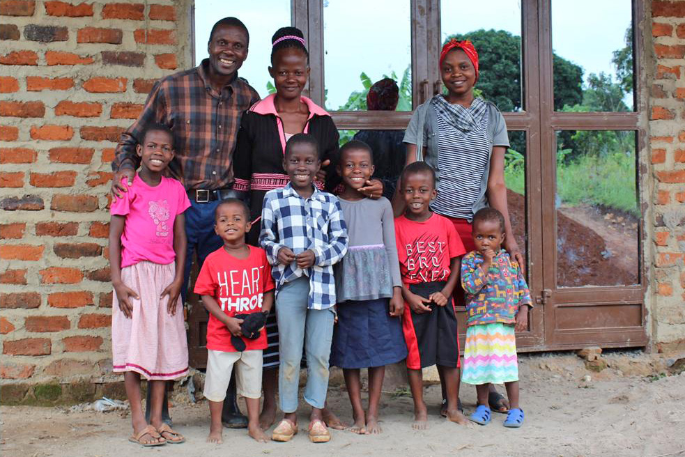 Allan Kisakye, his Wife, Harriet, and their Six Children in Front of the New Home They Built near the EWCV Property