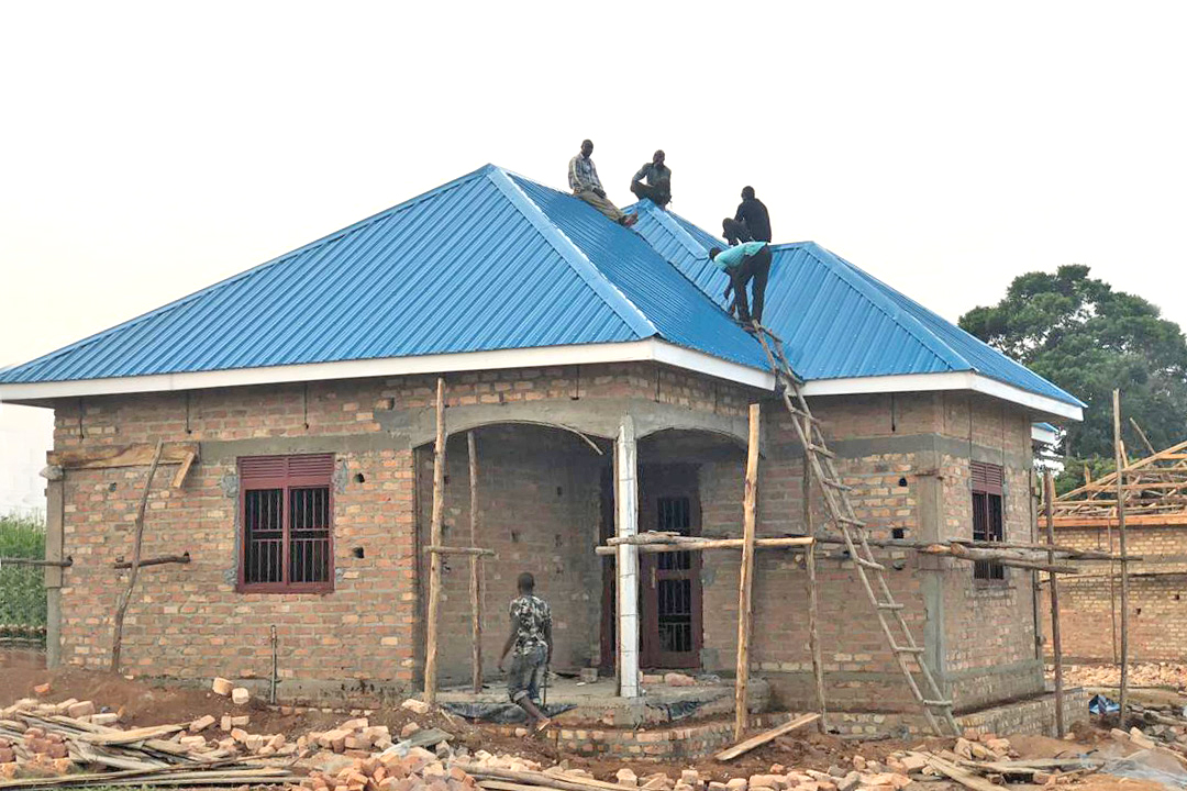 Workmen Completing the Roofing on the Three-bedroom House