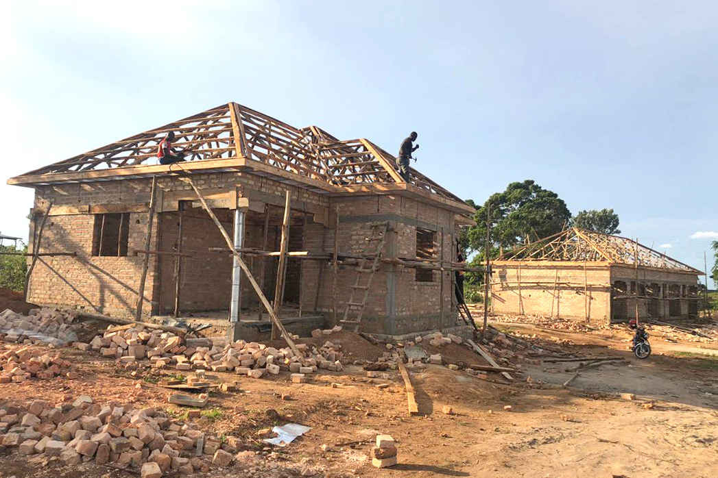 Men Working on Framing the Roofs on the Three-bedroom House and the Fourplex